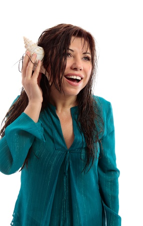 vivacious: A beautiful woman with wet skin and hair holding a seashell to her ear and with a vivacious open smile. Stock Photo