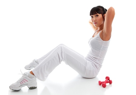 A young beautiful fit woman exercising or warming up.  She is on the floor performing sit ups crunches.  White background. Stock Photo - 9013475
