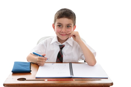 A happy young school student 6 year old boy sitting at school desk and smiling