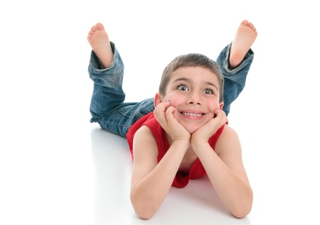 knees bent: A young bright eyed attentive boy smiling.  He is denim jeans and a red tank top, lying on his stomach with head in both hands and legs bent at the knees.   White background.