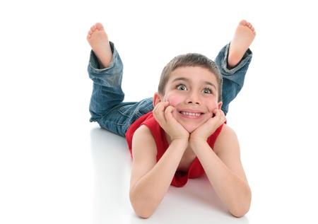 knees bent: Un giovane brillante eyed boy attento sorridente.  Egli � jeans denim e una canottiera rossa, sdraiato sulla pancia con testa in entrambi le mani e le gambe piegate le ginocchia.   Sfondo bianco.