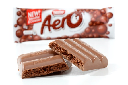 nestle: Nestle Aero chocolate bar Original 40g (450kj)  Showing product packaging at rear and chocolate bar content in focus in the foreground.  Milk chocolate with a light aerated bubbly centre.  Photographed in studio on a white background. Editorial