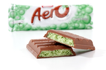 minty: Nestle Aero chocolate bar minty bubbles 40g (453kj) .  Showing wrapper packaging in background and pieces of the chocolate bar in focus in the foreground.  Photographed in studio on a white background. Editorial