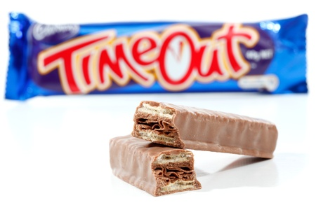 Cadbury Timout chocolate bar 40g (892kj)  Showing wrapper in background and chocolate contents in focus in the foreground.   Timeout consists of wafer biscuits with a flake chocolate centre and coated in milk chocolate.  Photographed in studio on a white  Stock Photo - 9115672