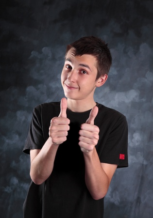 Young teen boy showing both thumbs up on a mottled background. Stock Photo - 9159828