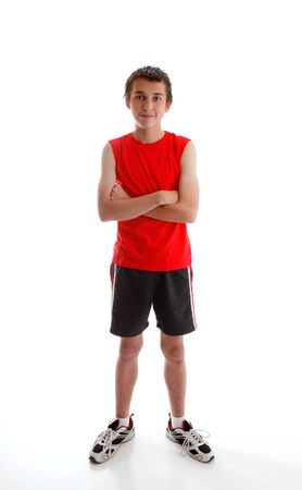 boy body: A young boy teenager wearing sports wear clothing, tank top, shorts and  sports shoes and standing with arms crossed.  White background.