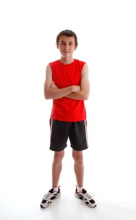Ein kleiner Junge Teenager tragen Sportwäsche Kleidung, Tank Top, Shorts und Sport Schuhe und ständigen mit Armen überquerte.  Weißer Hintergrund.