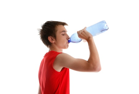 An active young boy teenager drinking bottled water after sport or exercise.  White background. Stock Photo - 9158406