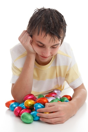 A boy looking down at lots of colourful bright chocolate easter eggs. Stock Photo - 9192476