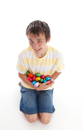 armful: Boy holding an armful of colorful chocolate easter eggs and smiling.  White background,