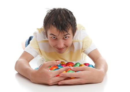A greedy or lucky boy hoarding lots of chocolate easter eggs.  White background.
