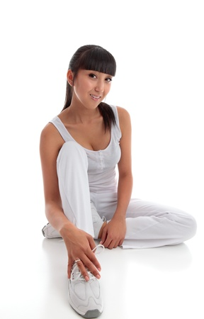 Beautiful smiling young woman wearing white exercise tracksuit pants, sports shoes and tanktop sits on the floor casually.  White background. Stock Photo - 9192468
