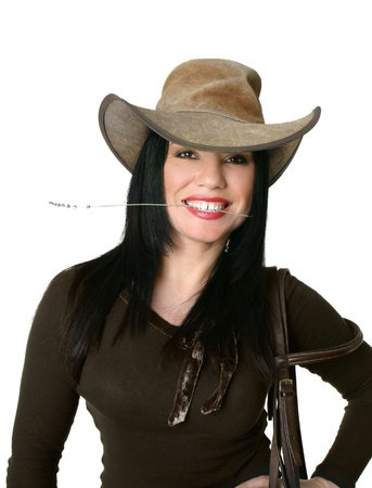 Smiling cowgirl wearing a leather western hat and carrying bridle. photo