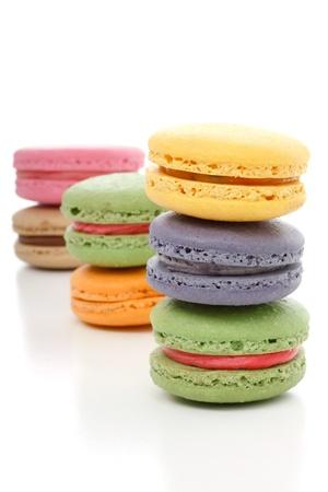 Die reizvolle leichte flaumige Textur Schmelzen im Mund mit ein wenig über Crunch und mit einer glatten Buttercreme Füllung - Mmmm Makronen.  Gestapelte auf weißem Grund. Verschiedenen Farben. Standard-Bild