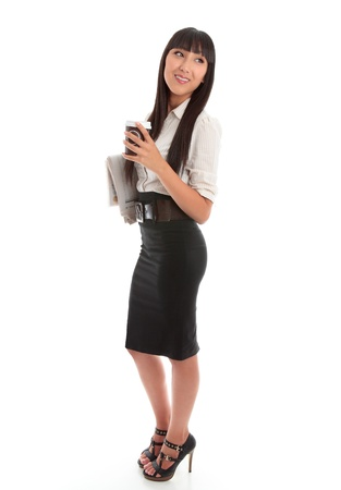 Smart businesswoman holding a takeaway coffee and financial newspaper.  She is looking over her shoulder and smiling confidently.    photo