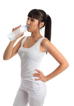 A young beautiful girl wearing white gym clothes is drinking refreshing water from a clear plastic bottle. White background. Stock Photo - 9814523