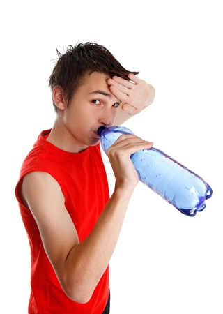 Teen boy wiping his brow and drinking water from a bottle. Stock Photo - 9964109