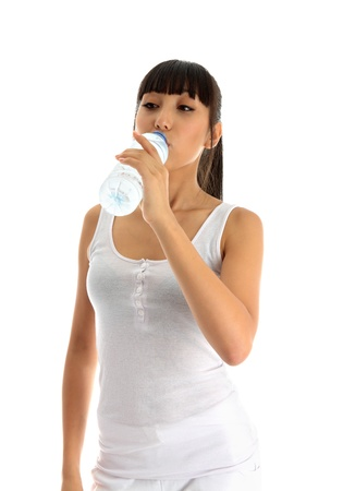 Pretty young woman drinking water from a plastic bottle photo