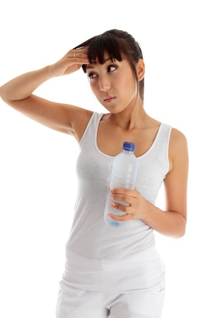 Young exhausted woman holding a bottle of water after workout. Stock Photo - 9964117