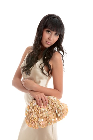 An attractive young woman wearing a gold silk dress and carrying a gold handbag.  She has long black hair.  White background. photo
