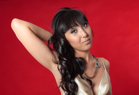 An alluring young woman wears a silk gold dress and necklace accessory. Red background. photo