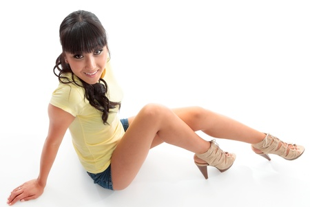 high heels woman: Sassy smiling woman sitting down wearing a tshirt and shots showing off her long legs.  White background.
