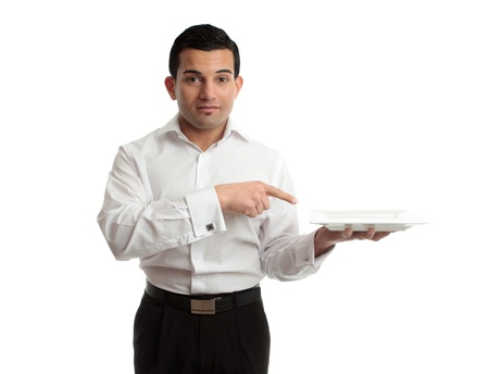 A waiter points to an empty white plate he is holding in his left hand. White background.
