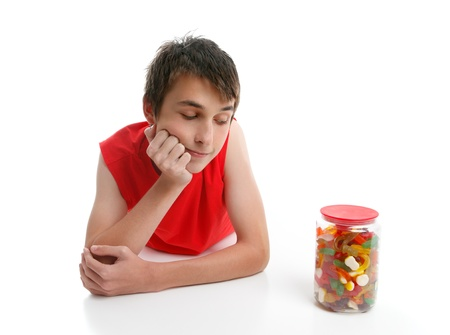 whether: A boy ponders whether to open a jar of assorted confectionery.  White background. Stock Photo