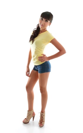 A young attractive girl wearing sexy denim shorts, gorgeous yellow t-shirt and laced high heels stands smiling with hand on one hip photo