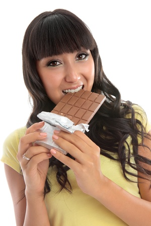 overindulgence: A young pretty woman biting into a block of fruit and nut fine chocolate.  White background.