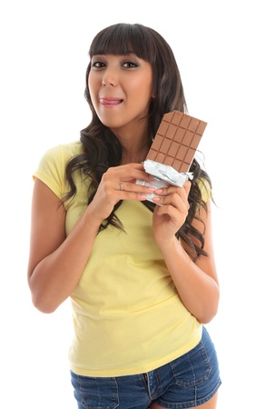 A pretty young beautiful woman holding a chocolate block and licking lips yum.  White background. photo