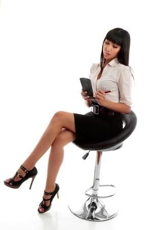 mujeres sentadas: Un joven muy elegante vestido empresaria o esten�grafo escribir notas o abreviada en un bloc de notas. Foto de archivo