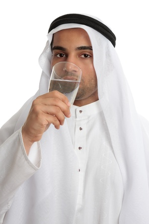 An arab middle eastern man wearing traditional clothing, is drinking a tall glass of clean fresh water. Water shortage stress from an increasing arab population and climate change compounding the problem has put pressure on providing safe clean fresh wate Banque d'images