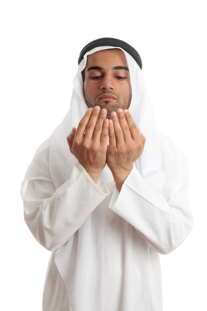 An arab middle eastern man dressed in traditional rob and headdress with open hands praying. photo