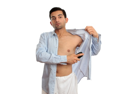 A man spraying a deodorant body spray under arms while getting dressed. photo