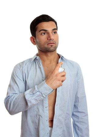 underarms: A man in the process of getting ready and dressed, sprays some cologne on skin.