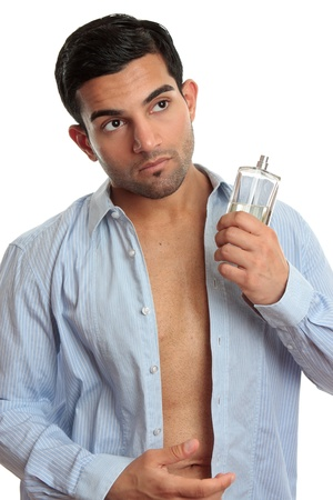 A man holding a bottle of cologne while getting dressed photo