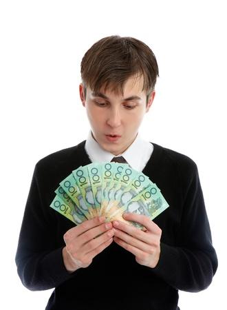 Ein Student oder junger Arbeiter suchen mit großer Verwunderung auf einen Fan von Banknoten in der Hand.