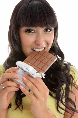 Closeup of a beautiful lively happy young woman eating from a chocolate block. Stock Photo - 10286305