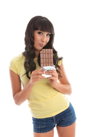 A beautful girl eating from a lblock of decadent chocolate.  White background Stock Photo - 10286304