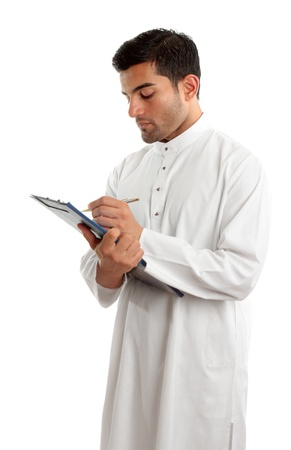 A traditionally dress middle eastern man writing in a clipboard folder.  White background. photo