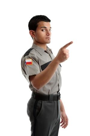 warden: Un guardia de seguridad, Alcaide de la prisi�n u otros uniformados hombre se�alando con su dedo en su mensaje.  Fondo blanco.