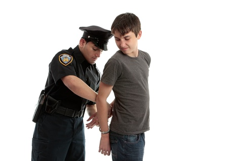 juvenile delinquent: A police officer arrests and handcuffs a young male teen felon.