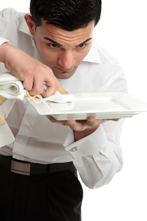 italian ethnicity: A male waiter servant or other hospitality staff worker is cleaning and polishing a white plate ready for service.