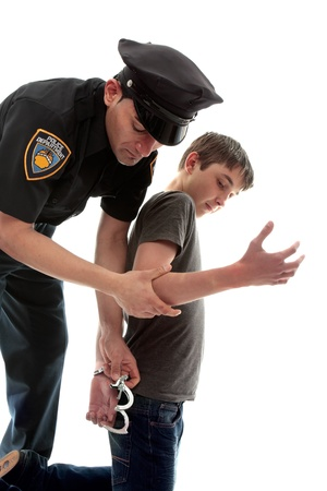A uniformed policeman arrests and handcuffs a young teen criminal
