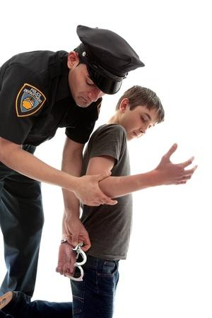 A uniformed policeman arrests and handcuffs a young teen criminal Banque d'images
