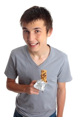 barra de cereal: Un sonriente niño sosteniendo un snack bar de muesli saludable. Foto de archivo