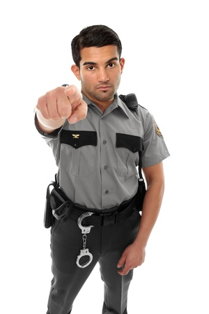 policeman: A police officer, prison guard or similar uniformed man stands firm with pointed finger.  Concept