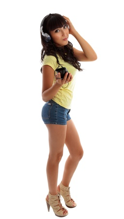A pretty girl dressed in denim shorts and a yellow t-shirt is listening to music on a portable mp3 player. photo
