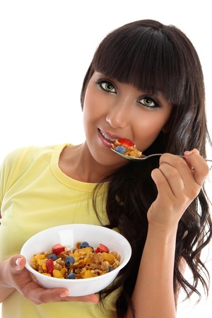 A female eating a healthy nutritional breakfast of cereals grains and fruit photo